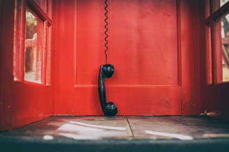 black handset hanging in a red telephone box